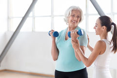 Cheerful persistent woman holding dumbbells. Physical strength. Pleasant confident joyful women holding rubber dumbbells and lifting them while building up her Royalty Free Stock Photo