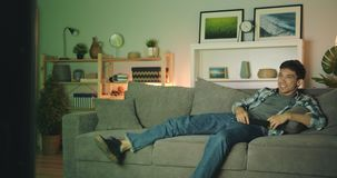 Cheerful person laughing watching tv chilling on couch in dark apartment