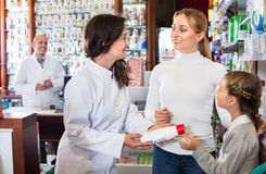 Cheerful pharmacist  the pharmaceutical store and consulting cus Stock Images