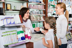 Cheerful pharmacist the pharmaceutical store and consulting cus. Cheerful pharmacist in white coat working the pharmaceutical store and consulting customers royalty free stock photography