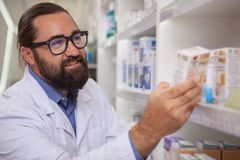 Cheerful pharmacist selling medication at his drugstore stock photo