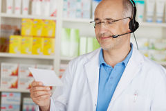 Cheerful pharmacist using headset. Pharmacist using headset and looking at prescription Stock Images