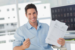 Cheerful photo editor pointing at documents. In his office stock photography