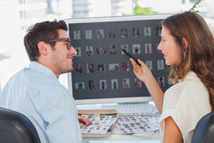 Cheerful photo editors working on thumbnails. In their office Royalty Free Stock Image
