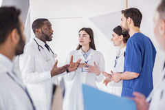 Cheerful physicians speaking at conference in clinic Stock Photos