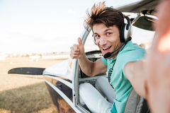 Cheerful pilot sitting in airplane cabin and showing thumbs up Royalty Free Stock Photography