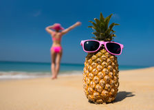 Cheerful pineapple glasses and a woman in a bikini sunbathing on the beach on sea backgrounde beach on sea background. Stock Image