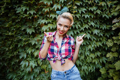 Cheerful pinup girl pointing away and on you in garden Royalty Free Stock Image
