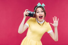 Cheerful pinup girl using vintage camera and taking pictures Stock Images