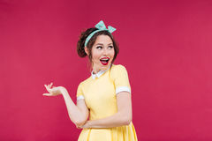 Cheerful playful pinup girl in yellow dress pointing away Stock Images