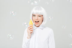 Cheerful playful young woman winking and holding fake ice cream Royalty Free Stock Photos