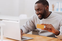 Cheerful pleasant man making an online payment Stock Photography