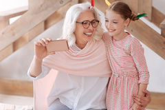 Cheerful pleasant woman hugging her granddaughter Stock Images