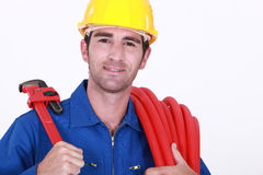 Cheerful plumber carrying hose Royalty Free Stock Images