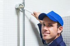 Cheerful plumber repairing shower head Stock Photo