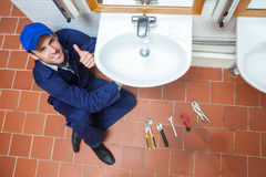 Cheerful plumber repairing sink showing thumb up Stock Photos