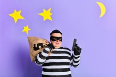 Cheerful plump man is being rejoiced at successful offence. Blue background. studio shot royalty free stock photo