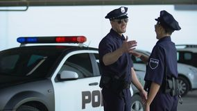 Cheerful policeman and policewoman giving high five to each other, teammates. Stock footage stock footage