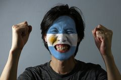 Cheerful portrait of a man with the flag of the Argentina painted on his face on grey background. The concept of sport or nationalism stock photo