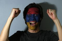 Cheerful portrait of a man with the flag of the Armenia painted on his face on grey background. The concept of sport or nationalism. horizontal tricolor of red royalty free stock image
