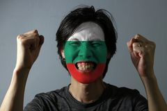 Cheerful portrait of a man with the flag of the Bulgaria painted on his face on grey background. The concept of sport or nationalism. white green and red color stock photos