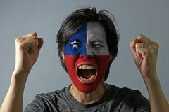 Cheerful portrait of a man with the flag of the Chile painted on his face on grey background. The concept of sport or nationalism stock photo