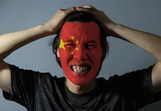 Cheerful portrait of a man with the flag of the China painted on his face on grey background. The concept of sport or nationalism. Large golden star within an stock photo