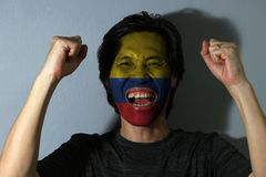 Cheerful portrait of a man with the flag of the Colombia painted on his face on grey background. The concept of sport or nationalism. tricolor of yellow double stock image