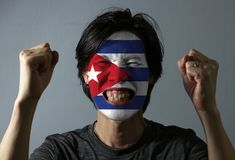 Cheerful portrait of a man with the flag of the Cuba painted on his face on grey background. The concept of sport or nationalism stock image
