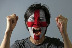 Cheerful portrait of a man with the flag of the England painted on his face on grey background. The concept of sport or nationalism. red centred cross on a royalty free stock photography