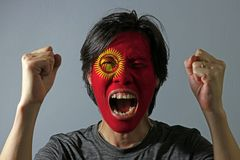 Cheerful portrait of a man with the flag of the Kyrgyzstan painted on his face on grey background. The concept of sport or nationalism royalty free stock image