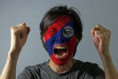 Cheerful portrait of a man with the flag of the Laos painted on his face on grey background. The concept of sport or nationalism stock photo