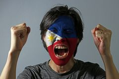 Cheerful portrait of a man with the flag of the Philippines painted on his face on grey background. The concept of sport or nationalism royalty free stock image