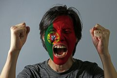 Cheerful portrait of a man with the flag of the Portugal painted on his face on grey background. The concept of sport or nationalism royalty free stock images