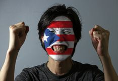 Cheerful portrait of a man with the flag of the Puerto Rico painted on his face on grey background. The concept of sport or nationalism stock photos
