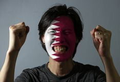 Cheerful portrait of a man with the flag of the Qatar painted on his face on grey background. The concept of sport or nationalism royalty free stock photography