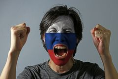 Cheerful portrait of a man with the flag of Russia painted on his face on grey background. The concept of sport or nationalism. white blue and red color stock photography
