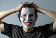 Cheerful portrait of a man with the flag of the South Korea painted on his face on grey background. The concept of sport or nationalism stock image