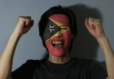 Cheerful portrait of a man with the flag of Timor Leste painted on his face on grey background. The concept of sport or nationalis. M. red yellow and black color royalty free stock images