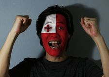 Cheerful portrait of a man with the flag of Tonga painted on his face on grey background. The concept of sport or nationalism. red field with the white royalty free stock photos