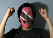 Cheerful portrait of a man with the flag of Trinidad and Tobago painted on his face on grey background. The concept of sport or nationalism. a red field with stock images