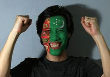 Cheerful portrait of a man with the flag of Turkmenistan painted on his face on grey background. The concept of sport or nationalism. five carpet guls stacked royalty free stock images