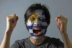 Cheerful portrait of a man with the flag of Uruguay painted on his face on grey background. The concept of sport or nationalism. white alternate with light stock photo