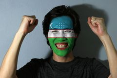 Cheerful portrait of a man with the flag of Uzbekistan painted on his face on grey background. The concept of sport or nationalism. horizontal bands of blue royalty free stock photo