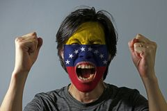 Cheerful portrait of a man with the flag of Venezuela painted on his face on grey background. The concept of sport or nationalism. royalty free stock photo
