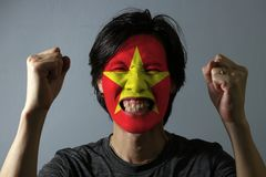 Cheerful portrait of a man with the flag of the Vietnam painted on his face on grey background. The concept of sport or nationalis. M. yellow star on red color royalty free stock photography