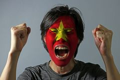 Cheerful portrait of a man with the flag of the Vietnam painted on his face on grey background. The concept of sport or nationalism. yellow star on red color stock image