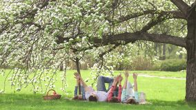 Cheerful portrait of a young family. Parents with their children lie under a blossoming apple tree. Family having fun on stock video footage