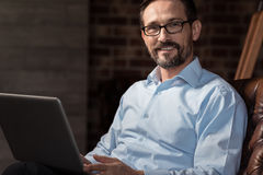 Cheerful positive businessman wearing glasses. Positive mood. Happy delighted handsome man smiling and looking at you while wearing glasses Royalty Free Stock Photos