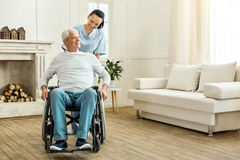 Cheerful positive caregiver moving a wheelchair. Time for a walk. Cheerful positive female caregiver standing behind her patient and moving a wheelchair while Royalty Free Stock Photography